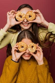Meninas felizes de vista frontal com donuts vitrificados