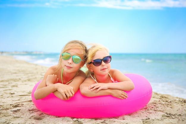 Meninas felizes, deitado no círculo inflável rosa na praia
