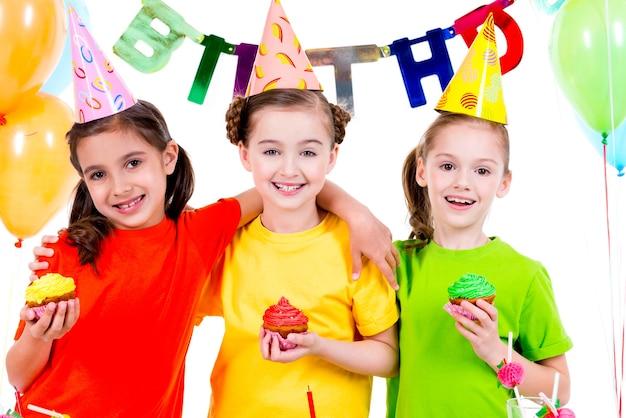 Meninas felizes e sorridentes segurando bolos coloridos - isolados em um fundo branco.