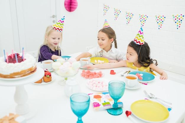 Meninas felizes em bonés de festa comendo doces na festa de aniversário
