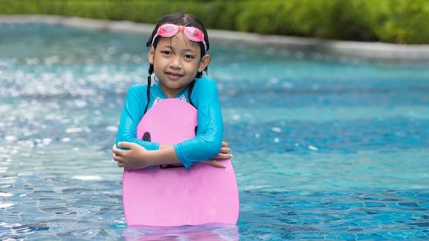Meninas felizes em trajes de banho em pé com kickboard na piscina