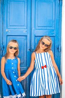 Meninas felizes em vestidos em uma rua de uma típica vila tradicional grega na ilha de mykonos, na grécia