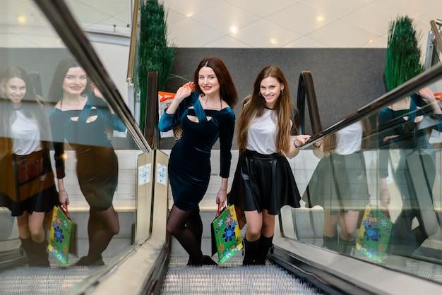 Meninas felizes estão comprando no shopping.