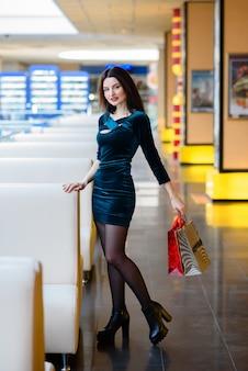 Meninas felizes estão fazendo compras no shopping.