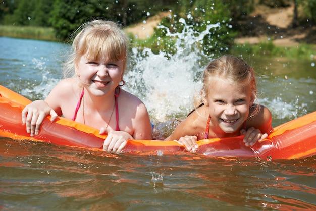 Meninas felizes no colchão no lago