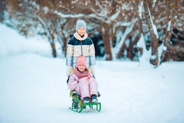 Meninas felizes pequenas adoráveis que sledding no dia nevado do inverno.