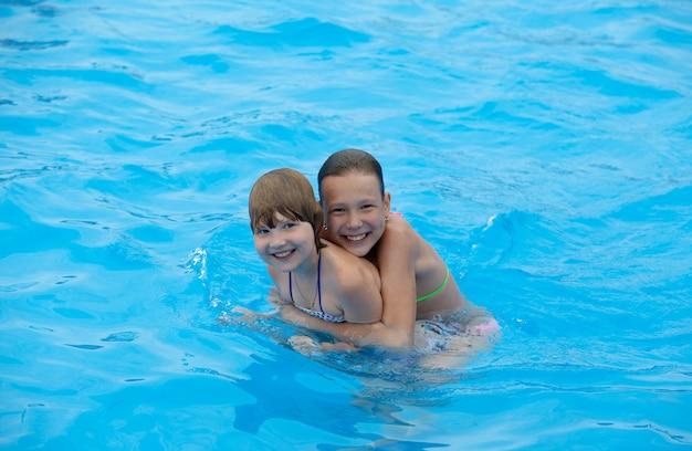 Meninas felizes se divertem nadando na piscina
