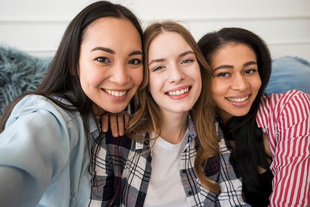 Meninas felizes tomando selfie e sorrindo olhando para a câmera
