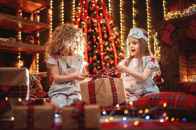 Meninas felizes vestindo pijamas de natal abrem a caixa de presente por uma lareira em uma aconchegante sala escura na véspera de natal.