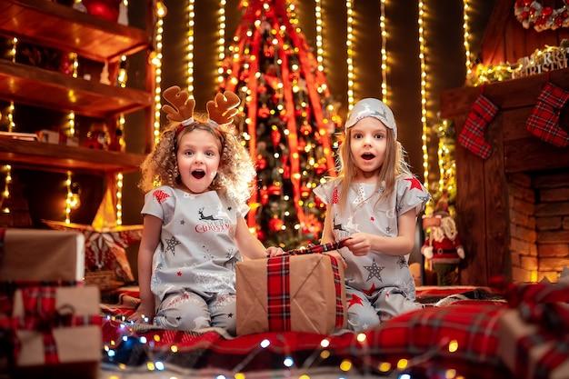 Meninas felizes vestindo pijamas de natal jogando junto a uma lareira em uma aconchegante sala escura na véspera de natal.