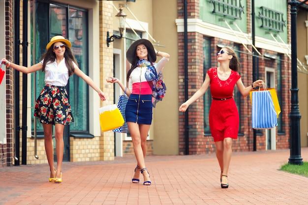 Meninas femininas muito felizes mulheres brilhantes em vestidos coloridos, chapéus e sapatos de salto altos com sacos de compras, andando na rua depois das compras