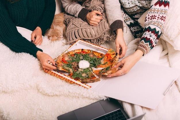 Meninas festejando com pizza, namoradas se divertindo comendo pizza e vendo filme