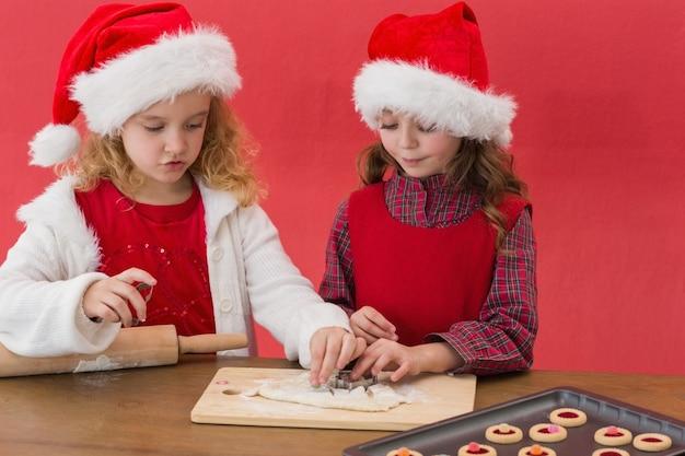 Meninas festivas que fazem biscoitos de natal