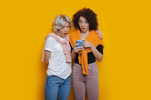 Meninas ficam maravilhadas com alguma coisa depois de olhar para o telefone