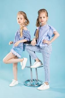 Meninas gêmeas em roupas azuis claras estão posando perto de um banquinho em um azul.
