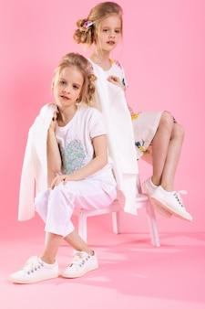 Meninas gêmeas em roupas brilhantes, posando perto da escada com duas etapas na rosa.