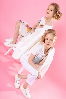 Meninas gêmeas em roupas brilhantes posando