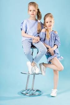 Meninas gêmeas em roupas de luz azuis estão posando
