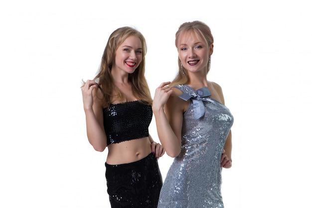 Meninas gêmeas loira linda posando em um branco em vestidos brilhantes, isolado