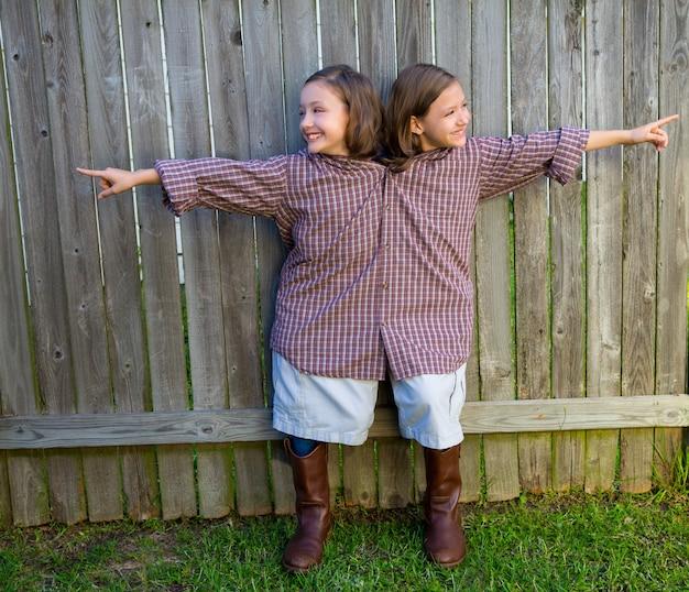 Meninas gêmeas vestidas como siameses com a camisa do pai