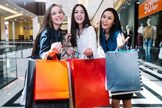 Meninas gesticulando na câmera no shopping center
