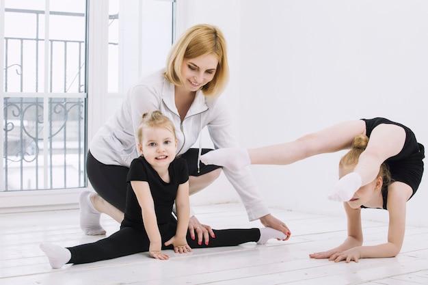 Meninas ginastas e dançarinas fazendo alongamento com uma treinadora em uma sala iluminada, felizes e fofas