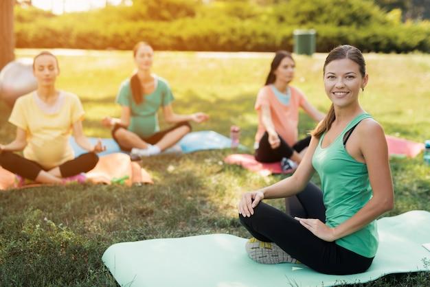 Meninas grávidas com instrutor de esporte na yoga mats fazendo ioga.
