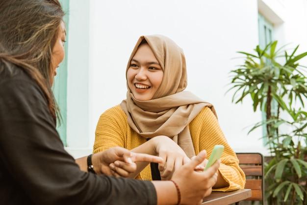 Meninas hijab vêem amigos enquanto conversam