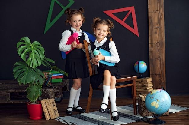 Meninas inteligentes com livros na escola