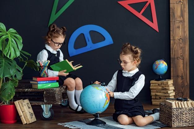Meninas inteligentes lendo livros e examinando o globo na escola