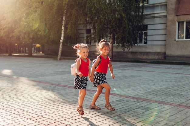 Meninas irmãs felizes vestindo mochilas e correndo. alunos de crianças se divertindo perto da escola. educação