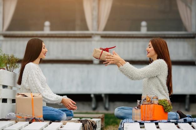 Meninas jogando um presente marrom entre eles