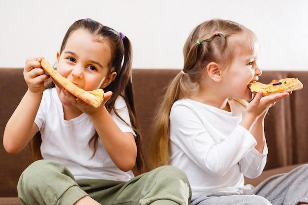 Meninas jovens, comendo pizza
