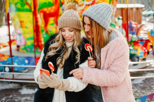 Meninas jovens e elegantes nas roupas de inverno estão andando na cidade solar com doces