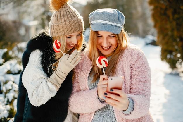 Meninas jovens e elegantes nas roupas de inverno estão andando no parque solar com candyes