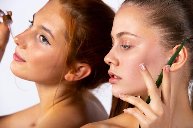 Meninas jovens e posando. foto ampliada. menina com folhas de aloe vera e uma pipeta com soro. conceito de beleza, spa e saúde. foto de alta qualidade