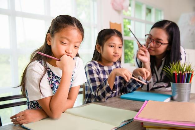 Meninas jovens estudantes sentem-se tristes e entediadas com um aviso estrito do professor na aula