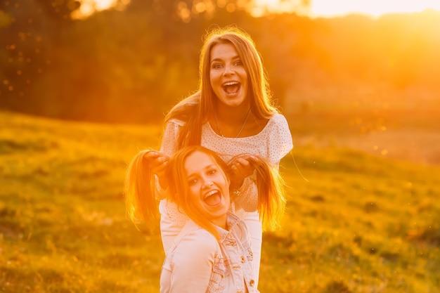 Meninas jovens fazem caretas engraçadas e olham para a lente da câmera no fundo da natureza à noite