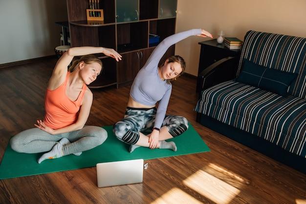 Meninas jovens fazendo exercícios de fitness com ajuda de programas de treinamento on-line no laptop