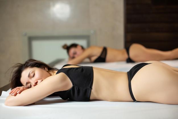 Meninas jovens lindas modelo em espreguiçadeiras de madeira relaxantes em uma sauna. estilo de vida de beleza e bem-estar