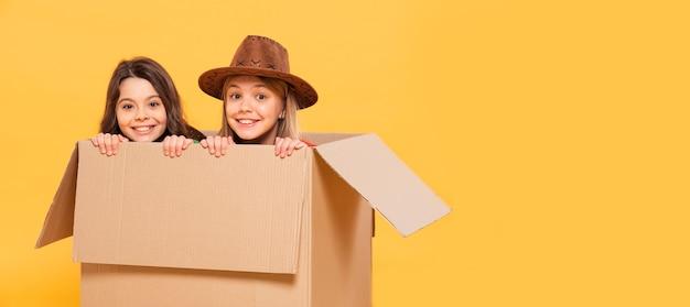 Meninas jovens, sentado na caixa dos desenhos animados