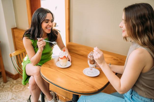 Meninas latinas sentadas em um café ouvindo a história de vida engraçada de uma amiga