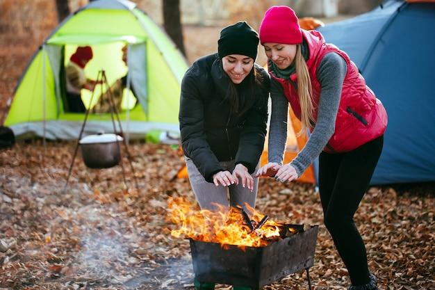 Meninas lésbicas são aquecidas pelo fogo em um fundo de jogar as crianças