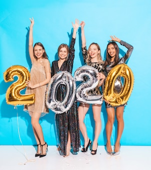 Meninas lindas felizes em elegantes vestidos de festa sexy segurando balões de ouro e prata 2020