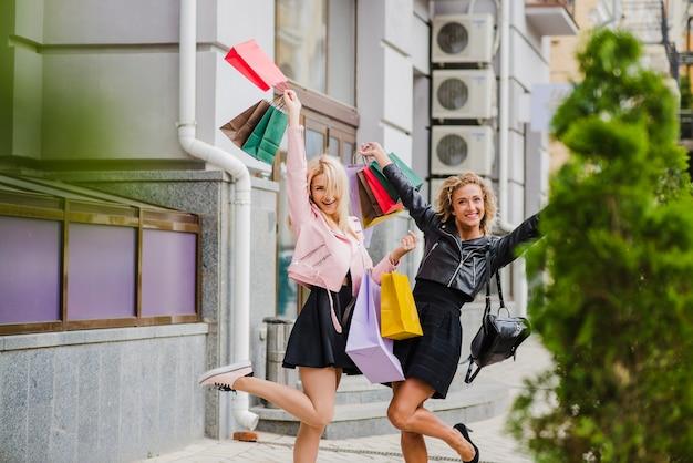 Meninas loiras sorridentes com sacos de compras em pé