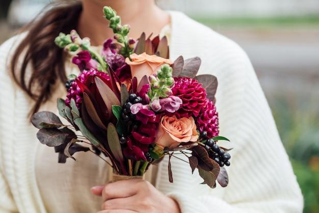 Meninas mãos segurando buquê de flores em estilo boho rústico