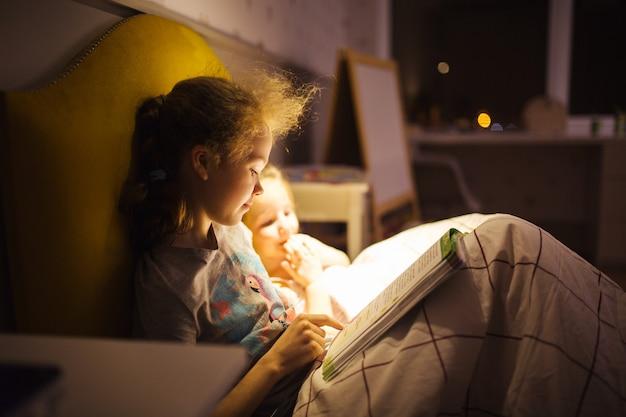 Meninas melhores amigas lêem conto de fadas antes de dormir. melhores livros para crianças. irmãs ler o livro na cama. tradição familiar.