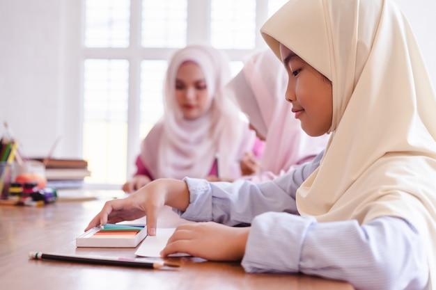 Meninas muçulmanas asiáticas bonitos que pintam e que desenham na sala de aula.