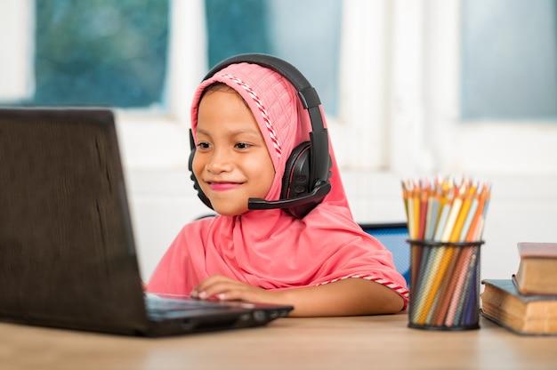 Meninas muçulmanas estudando online em casa para reduzir a distância social e prevenir doenças transmissíveis