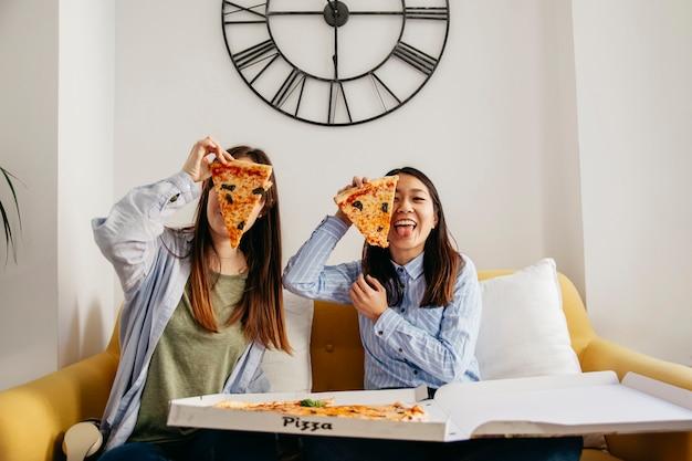 Meninas muito casuais divertindo-se com pizza